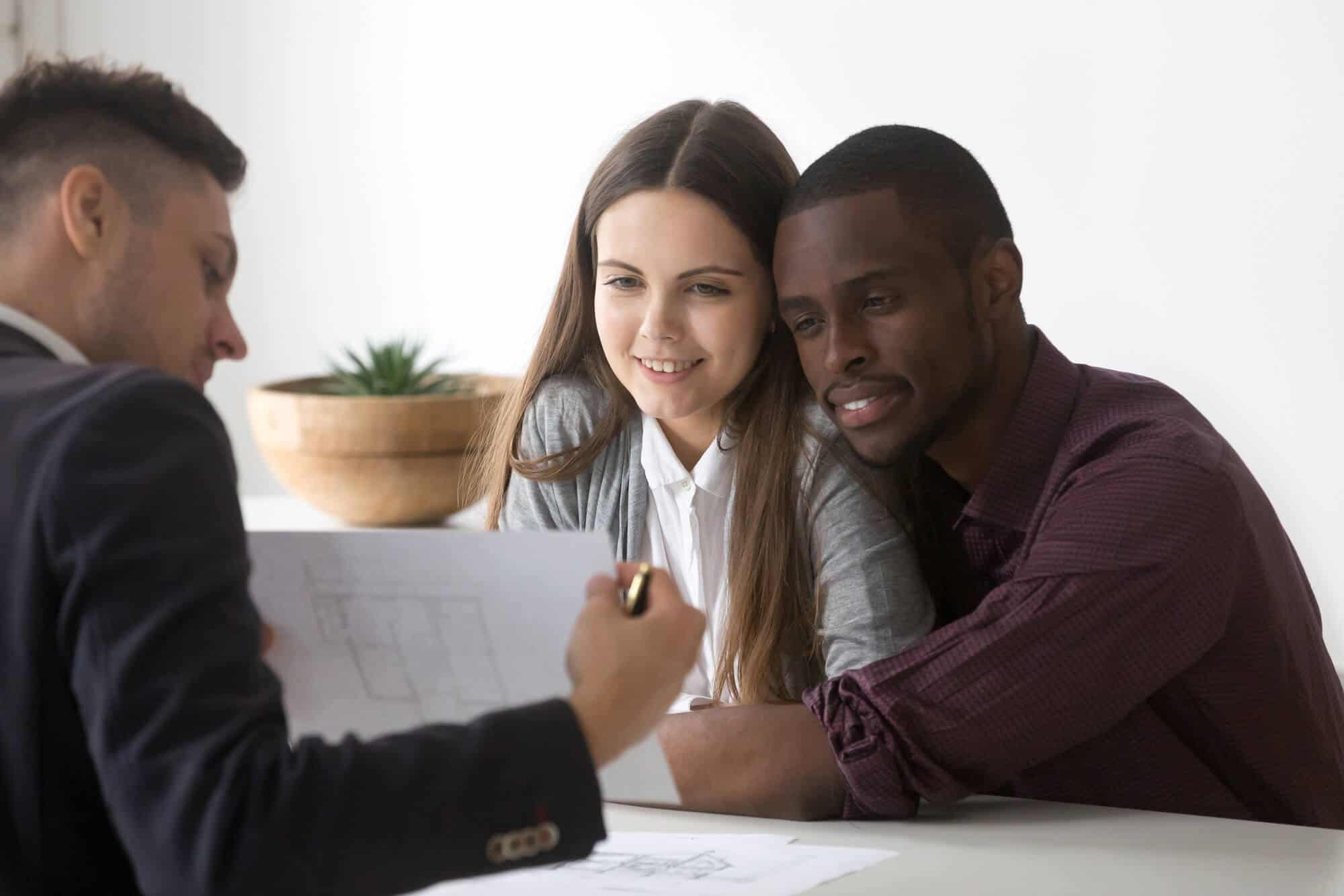 Male real estate agent or consultant showing house plan to happy millennial multiracial couple buying first home together, architect discussing apartment design with spouses or young family